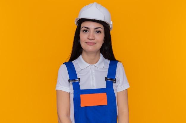 Jonge bouwersvrouw in eenvormige bouw en veiligheidshelm die voorzijde glimlachend zelfverzekerd over oranje muur bekijken