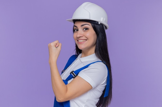 Jonge bouwersvrouw in eenvormige bouw en veiligheidshelm die voorzijde glimlachend zelfverzekerd tonen die vuist bekijken die zich over purpere muur bevinden