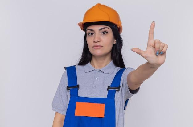 Jonge bouwersvrouw in eenvormige bouw en veiligheidshelm die voorzijde met ernstig gezicht bekijken die wijsvingerwaarschuwing tonen die zich over witte muur bevinden