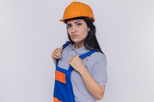 Jonge bouwersvrouw in eenvormige bouw en veiligheidshelm die voorzijde met ernstige zekere uitdrukking bekijkt die zich over witte muur bevindt