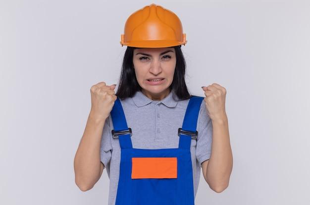 Jonge bouwersvrouw in eenvormige bouw en veiligheidshelm die voorzijde met gebalde vuisten boos en gefrustreerd bekijken die zich over witte muur bevinden