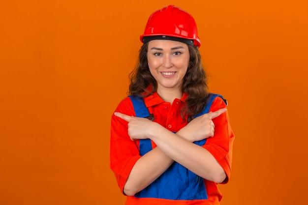 Jonge bouwersvrouw in eenvormige bouw en veiligheidshelm die zich met gekruiste wapens bevinden en met wijsvingers aan andere kanten richten die over geïsoleerde oranje muur glimlachen
