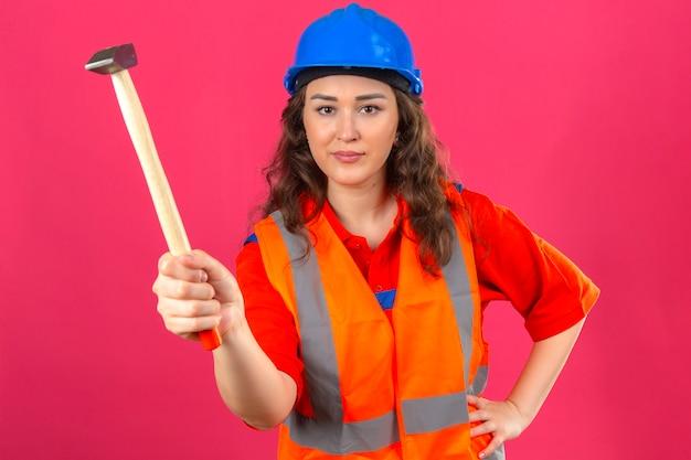 Jonge bouwersvrouw in eenvormige bouw en veiligheidshelm die zich met hamer bevinden die met glimlach camera over geïsoleerde roze muur bekijken