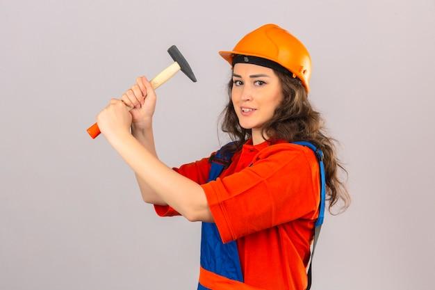 Jonge bouwersvrouw in eenvormige bouw en veiligheidshelm die zich met hamer bevinden die met het over geïsoleerde witte muur dreigen te raken