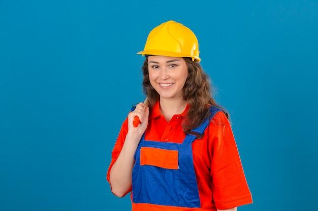 Jonge bouwersvrouw in eenvormige bouw en veiligheidshelm die zich met hamer op schouder bevinden die en gelukkig over geïsoleerde blauwe muur glimlachen