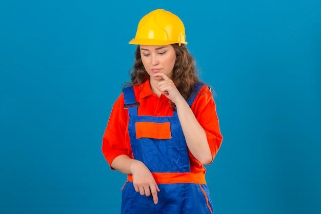 Jonge bouwersvrouw in eenvormige bouw en veiligheidshelm die zich met hand op kin bevindt die onderaan denkend hebbend over geïsoleerde blauwe muur kijkt