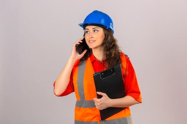 Jonge bouwersvrouw in eenvormige bouw en veiligheidshelm die zich met klembord bevinden die op mobiele telefoon over geïsoleerde witte muur spreken