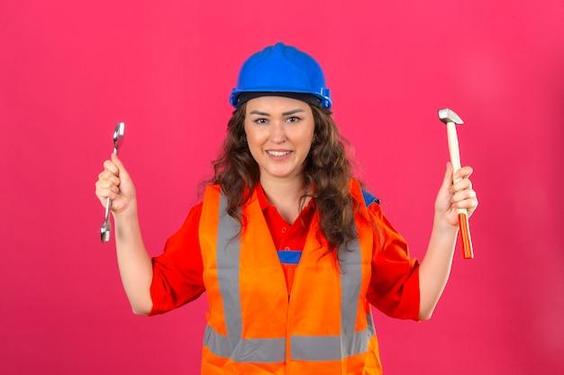 Jonge bouwersvrouw in eenvormige bouw en veiligheidshelm die zich met moersleutel en hamer in het opgeheven handen glimlachen bevinden vriendschappelijk over geïsoleerde roze muur