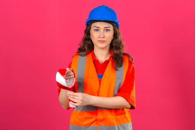 Jonge bouwersvrouw in eenvormige bouw en veiligheidshelm die zich met plakband met ernstig gezicht over geïsoleerde roze wall_ bevinden