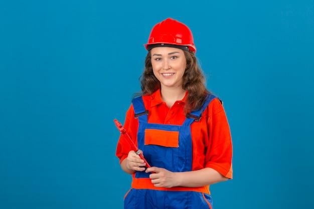 Jonge bouwersvrouw in eenvormige bouw en veiligheidshelm die zich met regelbare moersleutel bevinden die gelukkig en vriendschappelijk over geïsoleerde blauwe muur glimlachen kijken