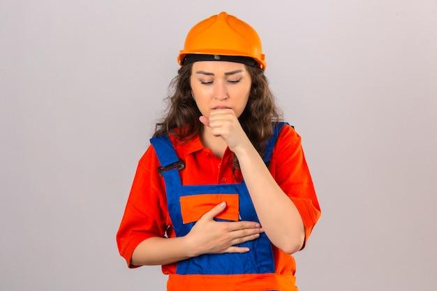 Jonge bouwersvrouw in eenvormige bouw en veiligheidshelm die zich onwel voelen en over geïsoleerde witte muur hoesten