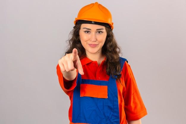 Jonge bouwersvrouw in eenvormige bouw en veiligheidshelm glimlachen die met vinger aan de camera over geïsoleerde witte muur richten