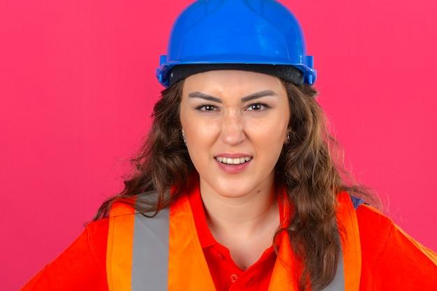Jonge bouwersvrouw in eenvormige bouw en veiligheidshelm met boze uitdrukking over geïsoleerde roze muur