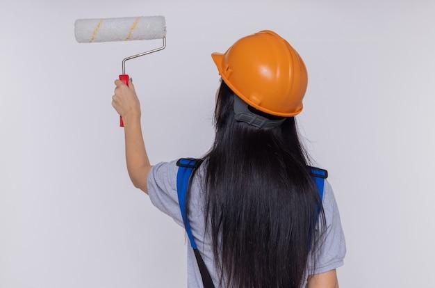 Jonge bouwersvrouw in eenvormige bouw en veiligheidshelm status