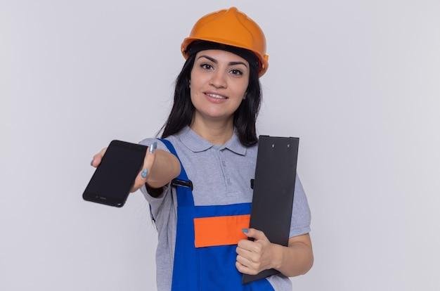 Jonge bouwersvrouw in eenvormige bouw en veiligheidshelm
