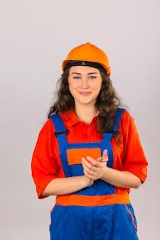 Jonge bouwersvrouw in eenvormige bouw en veiligheidshelmen die palmen wrijven en het glimlachen zeker over geïsoleerde witte muur kijken