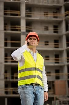 Jonge bouwingenieur die telefonisch op de bouwplaats praat