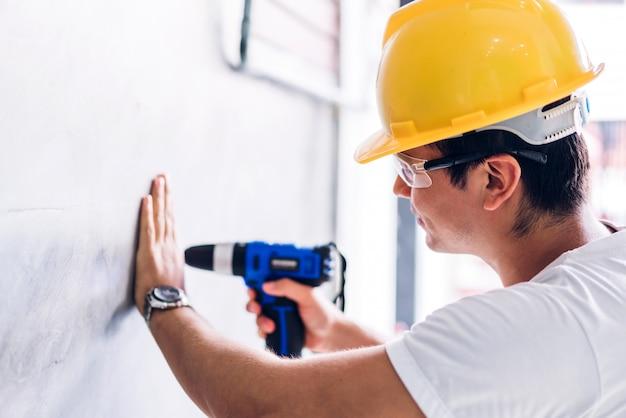 Jonge bouwvakker die met schroevedraaier werkt om in een huisingang te boren