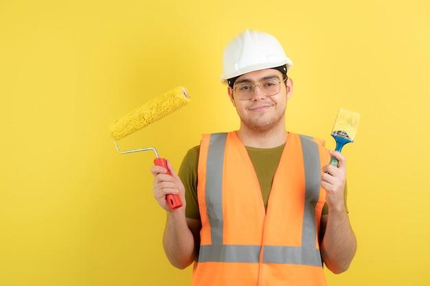 Jonge bouwvakker in bouwvakker schilderij roll en penseel te houden.