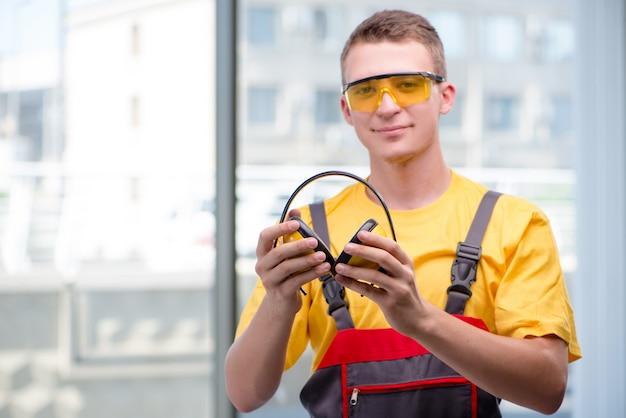 Jonge bouwvakker in gele overall