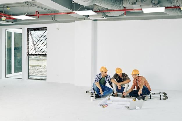 Jonge bouwvakkers zittend op de ladder met blauwdrukken en kleurenpalet voor hen en planning van de werkzaamheden