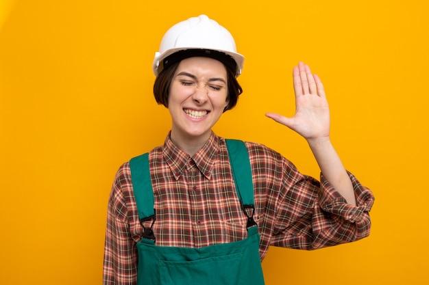 Jonge bouwvrouw in bouwuniform en veiligheidshelm blij en opgewonden glimlachend vrolijk met open palm die over oranje muur staat