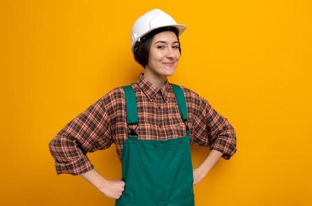 Jonge bouwvrouw in bouwuniform en veiligheidshelm blij en positief glimlachend vrolijk met handen op de heup die op oranje staat