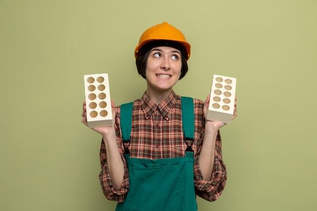 Jonge bouwvrouw in bouwuniform en veiligheidshelm die bakstenen vasthoudt en verward opzij kijkt terwijl ze op groen staat