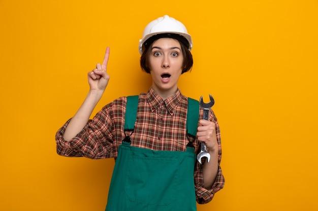 Jonge bouwvrouw in bouwuniform en veiligheidshelm die een moersleutel vasthoudt, verrast met het tonen van een wijsvinger met een nieuw idee dat op oranje staat