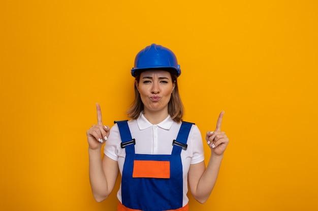 Jonge bouwvrouw in bouwuniform en veiligheidshelm die er verward uitziet met een groot gebaar met handen en vingers