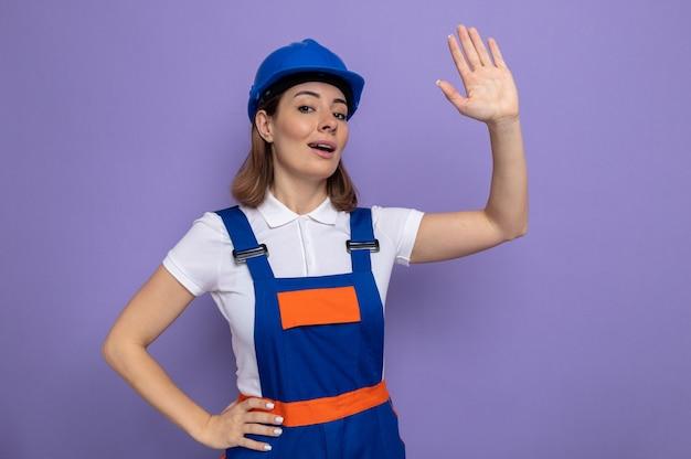 Jonge bouwvrouw in bouwuniform en veiligheidshelm die glimlachend zelfverzekerd zwaaiend met de hand kijkt