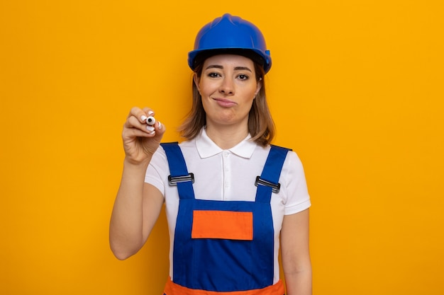 Jonge bouwvrouw in bouwuniform en veiligheidshelm die met een sceptische glimlach op het gezicht kijkt en met pen in de lucht schrijft