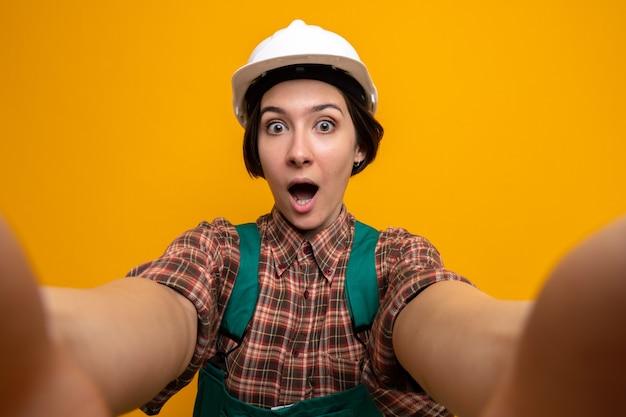 Jonge bouwvrouw in bouwuniform en veiligheidshelm die naar voren kijkt verbaasd en verrast over oranje muur