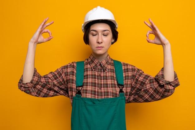Jonge bouwvrouw in bouwuniform en veiligheidshelm die ontspant en meditatiegebaar maakt met vingers met gesloten ogen op oranje
