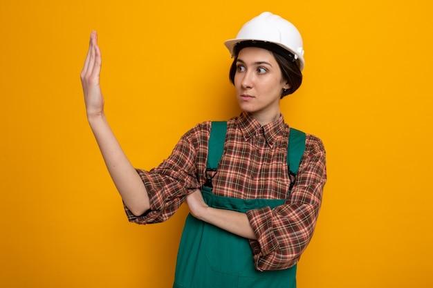 Jonge bouwvrouw in bouwuniform en veiligheidshelm die opzij kijkt naar haar hand, bezorgd en verward staande op oranje