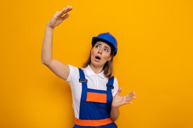 Jonge bouwvrouw in bouwuniform en veiligheidshelm die verbaasd en verrast kijkt en een groot gebaar maakt met handen die over de oranje muur staan