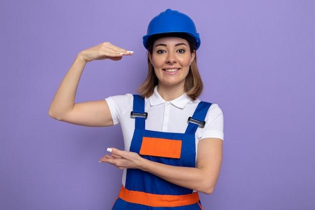 Jonge bouwvrouw in bouwuniform en veiligheidshelm die zelfverzekerd glimlacht en maatgebaar toont met handen die over paarse muur staan