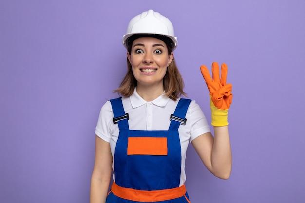 Jonge bouwvrouw in bouwuniform en veiligheidshelm in rubberen handschoenen, blij en vrolijk lachend met nummer drie met vingers over paarse muur