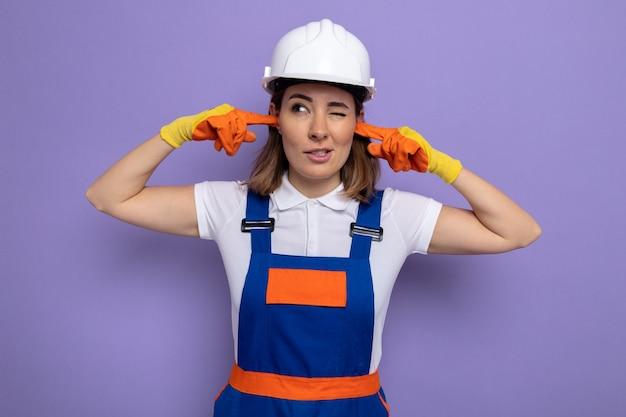 Jonge bouwvrouw in bouwuniform en veiligheidshelm in rubberen handschoenen die oren bedekken met vingers met geïrriteerde uitdrukking