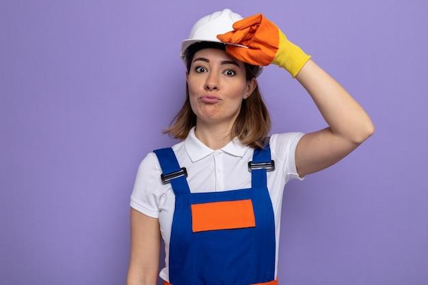 Jonge bouwvrouw in bouwuniform en veiligheidshelm in rubberen handschoenen die verward saluerend kijkt