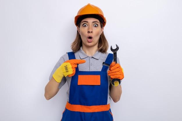 Jonge bouwvrouw in bouwuniform en veiligheidshelm in rubberen handschoenen met moersleutel die met wijsvinger erop wijst en er verbaasd uitziet terwijl ze op wit staat