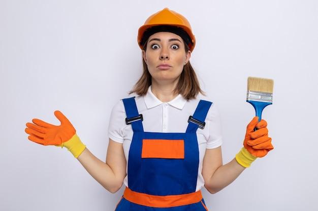 Jonge bouwvrouw in bouwuniform en veiligheidshelm in rubberen handschoenen met verfborstel verward schouders ophalend over witte muur