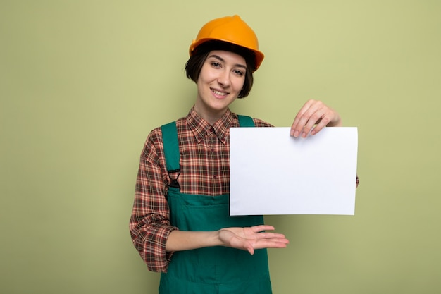 Jonge bouwvrouw in bouwuniform en veiligheidshelm met blanco pagina die presenteert met een arm van de hand die vrolijk lacht op groen