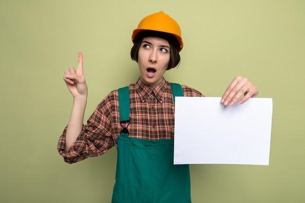 Jonge bouwvrouw in bouwuniform en veiligheidshelm met blanco pagina die verbaasd opkijkt en wijsvinger op groen laat zien