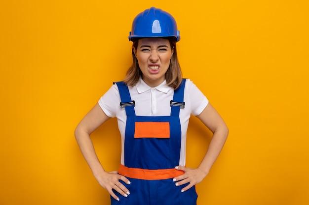 Jonge bouwvrouw in bouwuniform en veiligheidshelm met boos gezicht met armen op heup staande op oranje