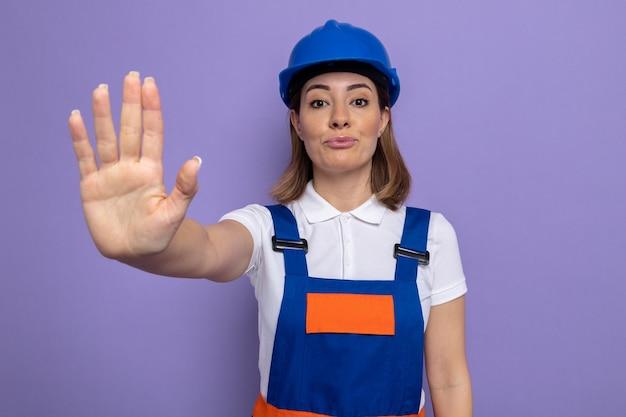 Jonge bouwvrouw in bouwuniform en veiligheidshelm met een serieus gezicht dat een stopgebaar maakt met de hand die over de paarse muur staat