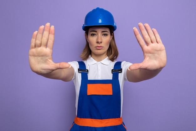 Jonge bouwvrouw in bouwuniform en veiligheidshelm met een serieus gezicht dat een stopgebaar maakt met handen die over de paarse muur staan
