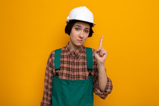 Jonge bouwvrouw in bouwuniform en veiligheidshelm met een serieus gezicht met wijsvinger die op oranje staat