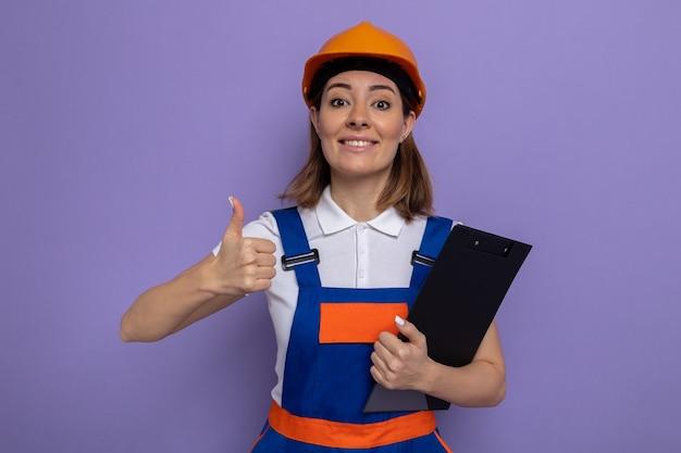 Jonge bouwvrouw in bouwuniform en veiligheidshelm met klembord glimlachend zelfverzekerd met duimen omhoog staand over paarse muur