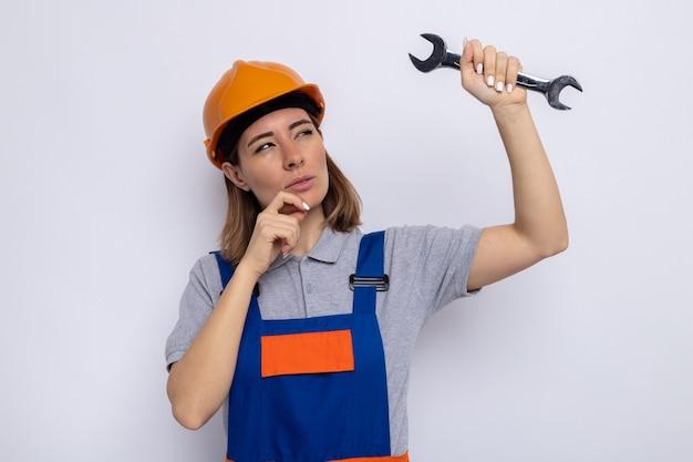 Jonge bouwvrouw in bouwuniform en veiligheidshelm met moersleutel die er verbaasd naar kijkt